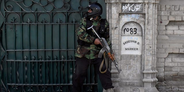 A policeman takes position after gunmen attacked the Bethel Memorial Methodist Church in Quetta, Pakistan.
