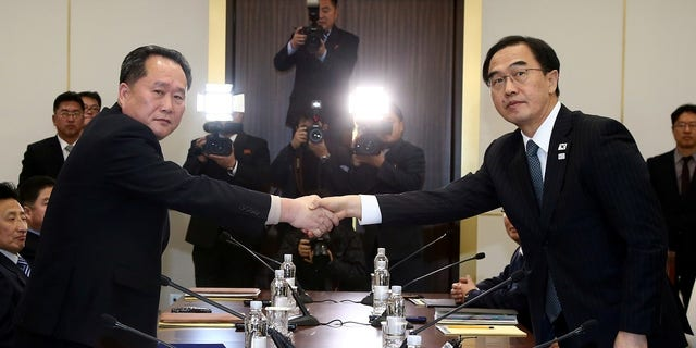 Head of the North Korean delegation, Ri Son Gwon, left, shakes hands with South Korean counterpart Cho Myoung-gyon.
