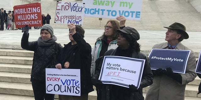 Activists rally outside the U.S. Supreme Court ahead of arguments in a key voting rights case involving a challenge to the Ohio's policy of purging infrequent voters from voter registration rolls.
