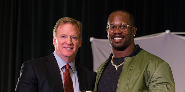 NFL commissioner Roger Goodell and Denver Broncos outside linebacker Von Miller hold the MVP Trophy.