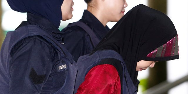 Indonesian Siti Aisyah, who is on trial for the killing of Kim Jong Nam, the estranged half-brother of North Korea's leader, is escorted as she arrives at the Shah Alam High Court.