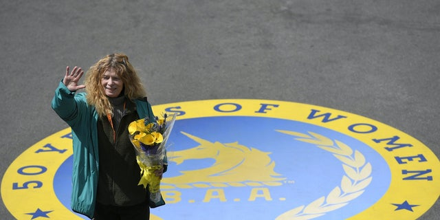 "Roberta ""Bobbi"" Gibb , the first woman to finish the Boston Marathon 50 years ago in 1966, waves to the crowd after ceremonially breaking a finish-line tape during the 120th running of the Boston Marathon in 2016."