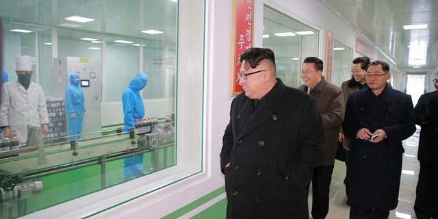 Kim Jong Un, accompanied by his wife Ri Sol Ju, gives field guidance at the Pyongyang Pharmaceutical Factory.