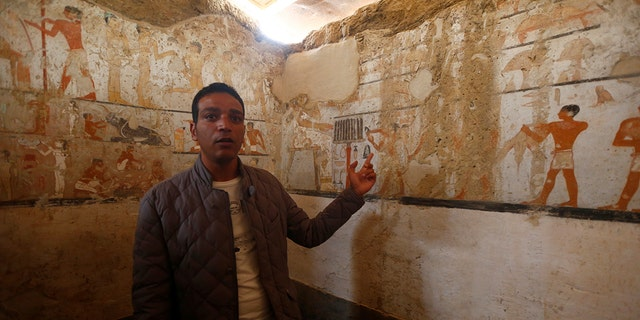 A guide from the Ministry of Antiquities inspects a discovery from Egypt's antiquities authorities at the Giza plateau, the site of the three ancient pyramids on the outskirts of Cairo, Egypt.