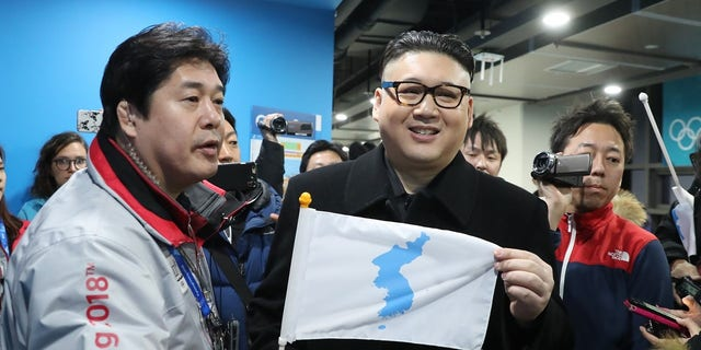 """The """"Kim"""" impersonator held up a unification flag after being kicked out of a ice hockey game."""