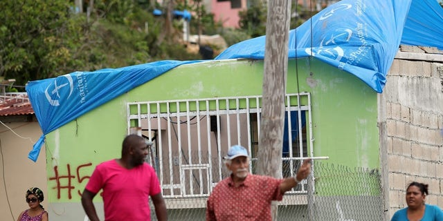 Residents stand near a house with a plastic sheet replacing the roof hit by Hurricane Maria in September.