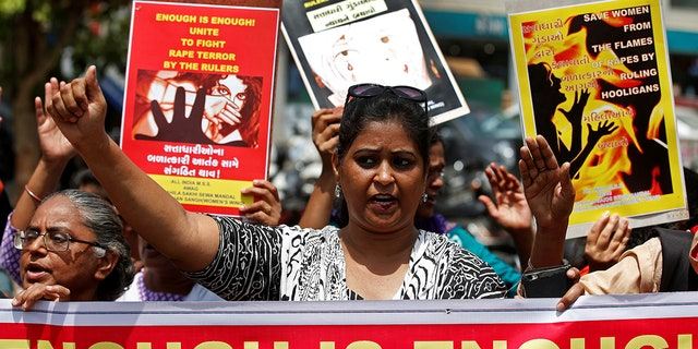 People hold placards at a protest against the rape of an eight-year-old girl.