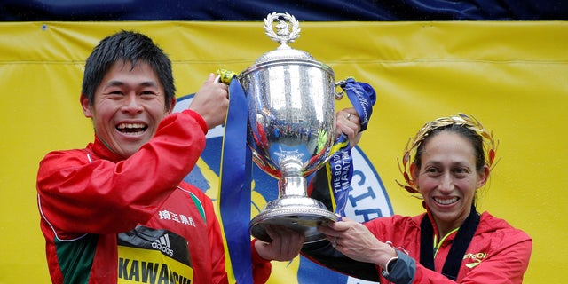 Yuki Kawauchi of Japan and Desiree Linden of the U.S. celebrate with the trophy after winning the men's and women's divisions of the 122nd Boston Marathon.