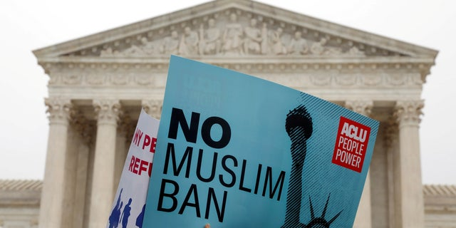 Protesters rally outside the U.S. Supreme Court, while the court justices consider case regarding presidential powers as it weighs the legality of President Trump's latest travel ban.