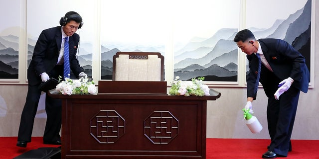 North Korean security officers check and prepare a desk before North Korean leader Kim Jong Un signs a guestbook at the truce village of Panmunjom inside the demilitarized zone separating the two Koreas, South Korea, April 27, 2018.