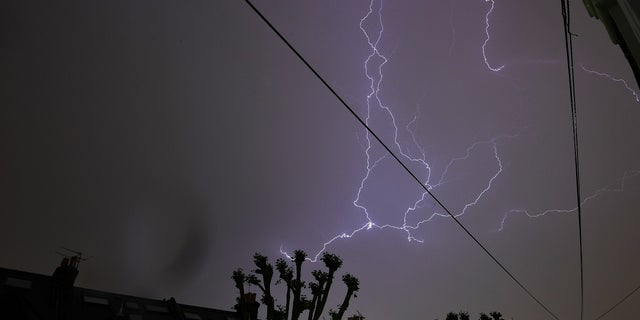 Lightning is seen from a bedroom window as it strikes above a street in south London.