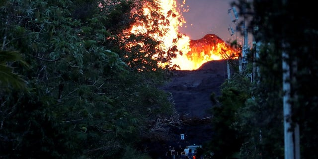 Onlookers gather at the foot of the lava bed, as a lava shoots molten rock into the air, in the Leilani Estates near Pahoa.