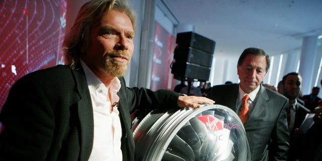 FILE -- Virgin founder and chairman Richard Branson poses with a bio-fuel Rolls-Royce Trent 1000 engine during an interview in New York, on March 3, 2008.