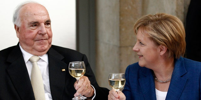 Helmut Kohl toasts with glasses of wine with German Chancellor Angela Merkel.