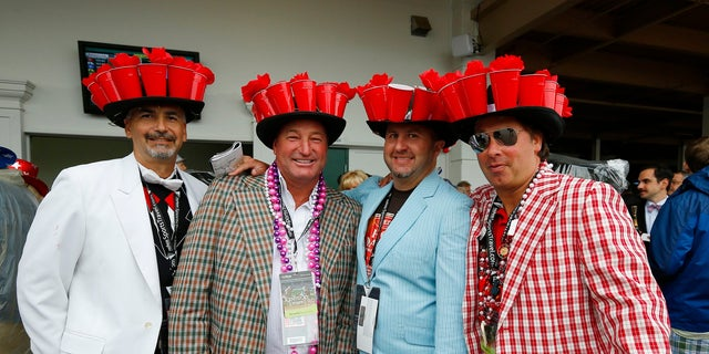 Attendees wear matching elaborate hats before the running of the 139th Kentucky Derby horse race at Churchill Downs.