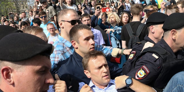 Russian police carrying struggling opposition leader Alexei Navalny, center, at a demonstration against President Vladimir Putin in Pushkin Square in Moscow, Russia, Saturday, May 5, 2018.