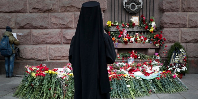 An Orthodox priest stands at a symbolic floral memorial near where a bomb blast tore through a subway train in St. Petersburg, Russia.
