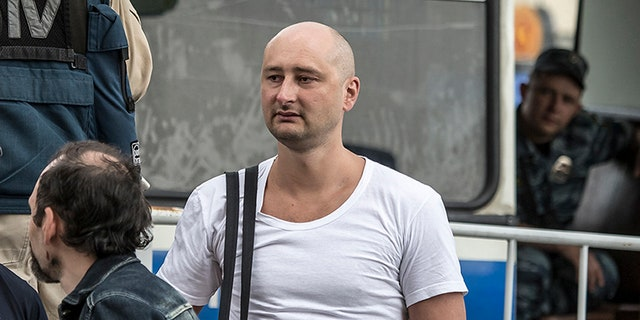 In this photo taken on Friday, May 31, 2013, Arkady Babchenko, 41, who had been scathingly critical of the Kremlin in recent years, stands at a police bus during an opposition rally in Moscow, Russia.