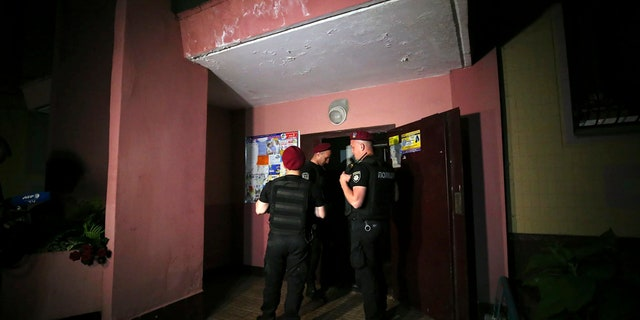 Police guard the front door of the multi-storey building where Russian opposition journalist Arkady Babchenko lived, in Kiev, Ukraine, Tuesday, May 29, 2018.