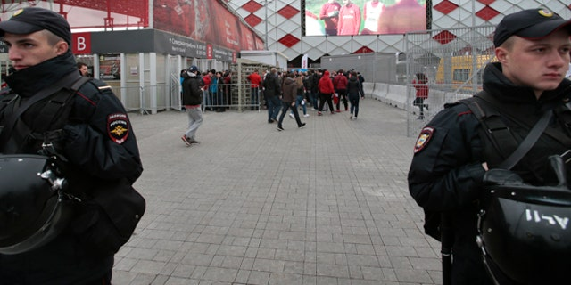 In this Wednesday, May 17, 2017 photo Russian police officers guard as fans arrive for a soccer match at Otkrytie Arena, stadium of Spartak Moscow soccer club, where Confederations Cup matches will be played, in Moscow, Russia. Terrorists, hooligans and anti-corruption protesters are among the main concerns for the Russian security forces during the Confederations Cup soccer tournament running from Saturday June 17 until Sunday July 2. (AP Photo/Ivan Sekretarev)