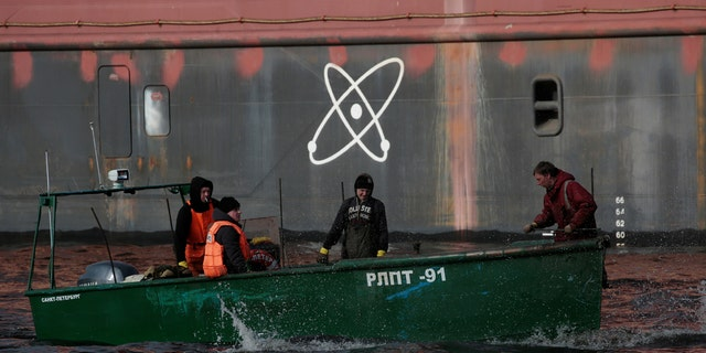 """Fishermen sail on a boat past the floating nuclear power plant """"Akademik Lomonosov"""", which is towed to an Atomflot base in Murmansk for nuclear fuel loading, in St. Petersburg, Russia April 28, 2018."""