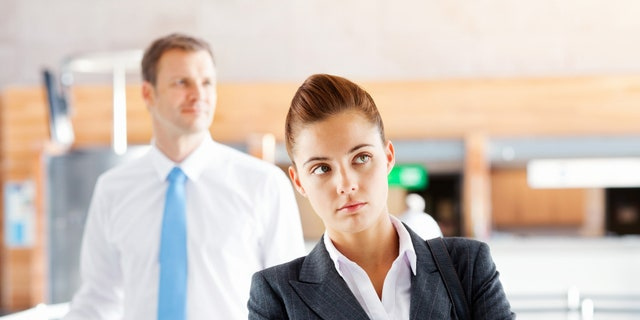 Frustrated businesswoman waiting with male executive standing in background at airport. Horizontal Shot.