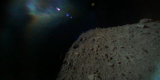 Image captured by Rover-1B on Sept. 21. This color image was taken immediately after separation from the spacecraft. The surface of Ryugu is in the lower right. The coloured blur in the top left is due to the reflection of sunlight when the image was taken. (Image credit: JAXA)