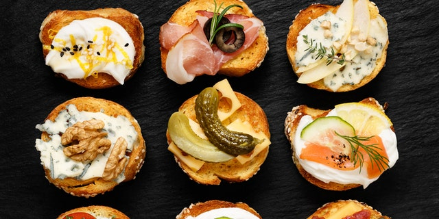Delicious appetizers with slices of  baguette and various toppings on stone black background