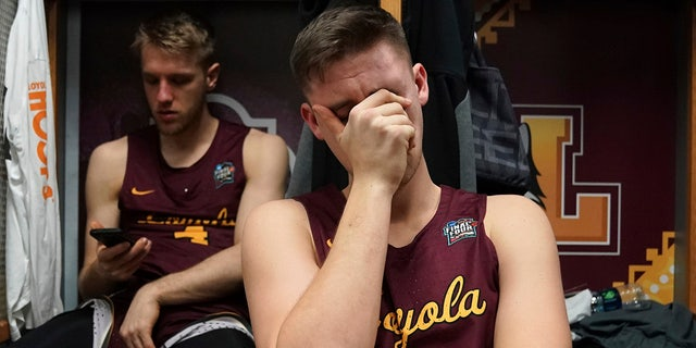 Loyola-Chicago's Carson Shanks (32) cries in the locker room after the semifinal game against Michigan.