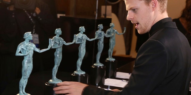 """Lucas Hedges, winner of the award for outstanding performance by a cast in a motion picture for """"Three Billboards Outside Ebbing, Missouri,"""" examines the SAG Award statues."""