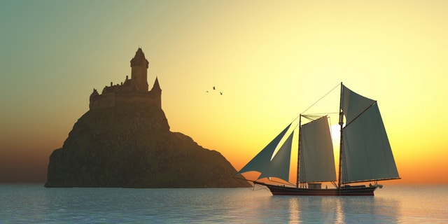 A schooner sails by a fortress castle on an island offshore from the coastline.