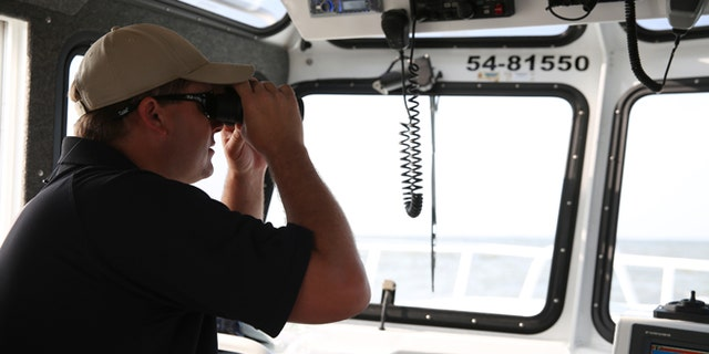 April 26, 2015: Lt. Jason Downey, of the Alabama Department of Conservation and Natural Resources, looks over the water during search and rescue operations off Dauphin Island, Ala.