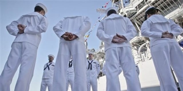 U.S. sailors of the USS Monterey stand next to their vessel in the Black Sea port of Constanta, Romania, Tuesday, June 7, 2011.