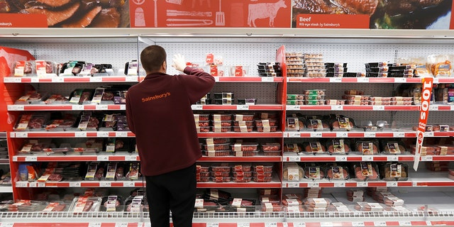 A Sainsbury's worker stacks a meat shelf in a store in Redhill, Britain, March 27, 2018.
