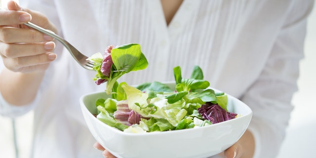 Close up shot of a woman holding a plate of fresh green salad in the beautiful morning light. She's holding a fork and she's about to eat the vegetarian food. Healthy eating and diet concept. Shallow depth of field with focus on the fork.