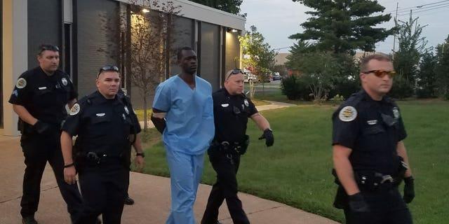 Police taking Samson, center, to jail.