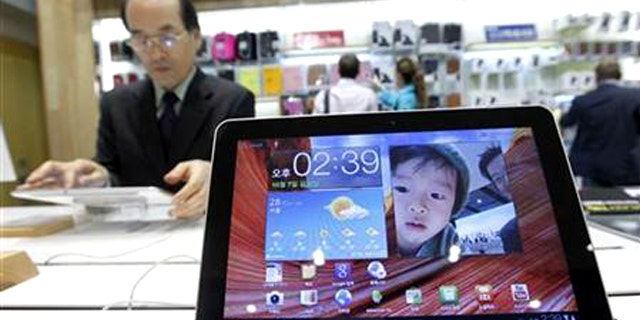 Oct. 7, 2011: A man uses Samsung Electronics' tablet Galaxy Tab 10.1 displayed for customers at the company's headquarters in Seoul.