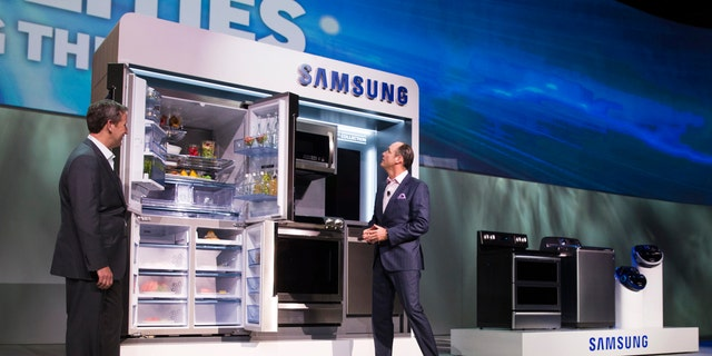John Herrington (L), senior vice president of Samsung Electronics America, and Tim Baxter, president of Samsung Electronics America, pose by Samsung Chef Collection kitchen appliances at a Samsung Electronics news conference during the 2015 International Consumer Electronics Show (CES) in Las Vegas, Nevada Jan. 5, 2015. (REUTERS/Steve Marcus)