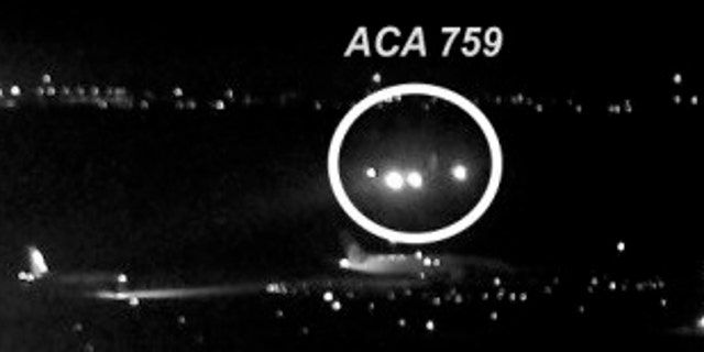 The image shows the Air Canada plane flying just above a United Airlines flight waiting on the taxiway. The jet came within 59 feet of the other planes.