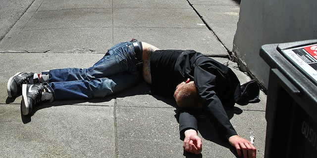 April 26, 2018: A man lies on the sidewalk beside a recyclable trash bin in San Francisco. The city's voters will decide in November 2018 whether to tax large businesses to pay for homeless and housing services in a city struggling with income inequality. Supporters collected enough signatures to get the measure on the ballot.