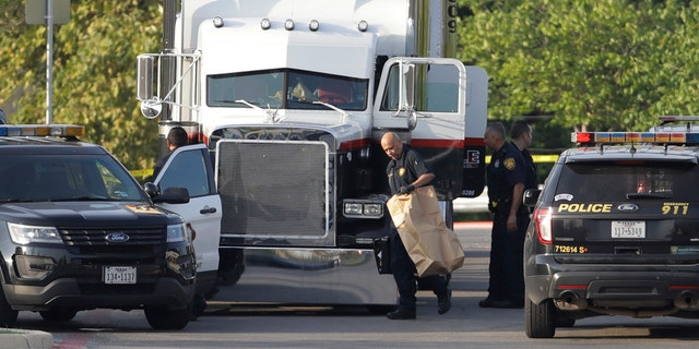 San Antonio police officers investigate the scene where eight people were found dead in a tractor-trailer loaded with at least 30 others outside a Walmart store.