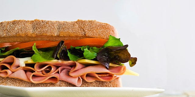 A gourmet sandwich of ham, cheese, lettuce, tomato and mayonaise isolated on white.