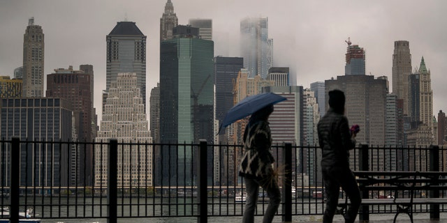Passersby walk on the Promenade in Brooklyn Heights, New York as rain and clouds loom over Manhattan on the fifth anniversary of Hurricane Sandy.