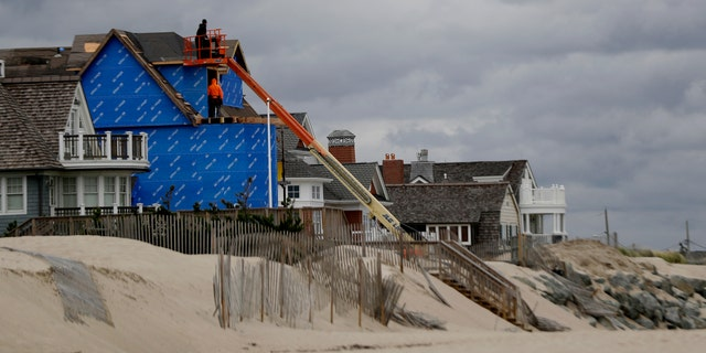 In a photo taken Thursday, Oct. 27, 2016, construction workers labor on a beachfront home in Bay Head, N.J.