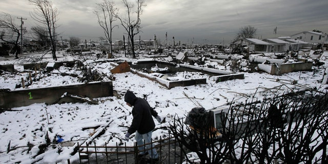 Nov. 8, 2012: Damon Rasinya carts debris from his family home past the fire-scorched landscape of Breezy Point after a Nor'easter snow in New York.