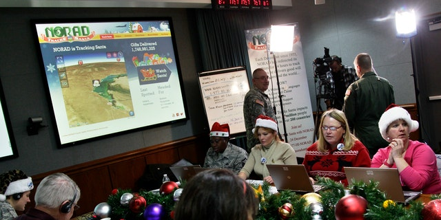 FILE - In this Dec. 24, 2012, file photo, volunteers take phone calls from children asking where Santa is and when he will deliver presents to their house, during the annual NORAD Tracks Santa Operation, at the North American Aerospace Defense Command, or NORAD, at Peterson Air Force Base, in Colorado Springs, Colo.The wildly popular NORAD Tracks Santa operation is launching its 61st run at Peterson Air Force Base, Colorado. Volunteers will answer phone calls and emails and post updates about Santa's storybook world tour on Facebook and Twitter. (AP Photo/Brennan Linsley, File)