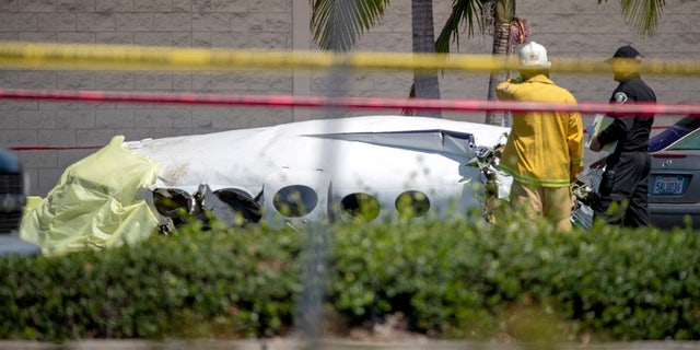 Santa Ana fire and police and Orange County Fire departments respond to the scene of a deadly plane crash in a parking lot.