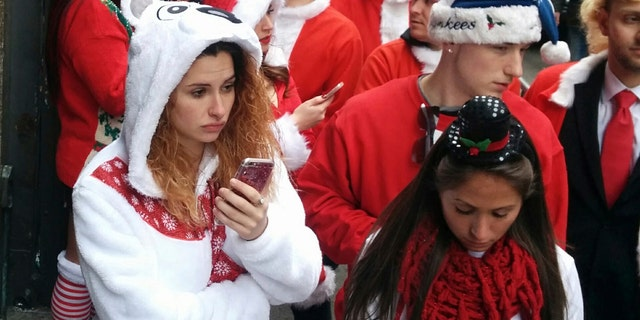 """Revelers line up to enter a tavern during the annual """"SantaCon"""" in New York on Saturday, Dec. 10, 2016.  SantaCon grew from a 1994 San Francisco """"Santarchy"""" that satirized Christmas consumerism into bashes in over 300 cities. (AP Photo/Julie Walker)"""