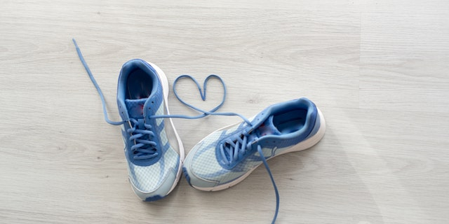 Love sign, Selective focus close up blue sport shoes on gray floor.