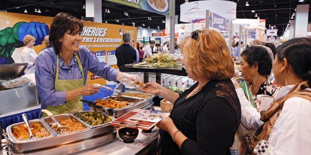 July 17, 2012: Diane Wagner, with Schwan Food Co., hands out samples at a booth during the School Nutrition Association conference in Denver.
